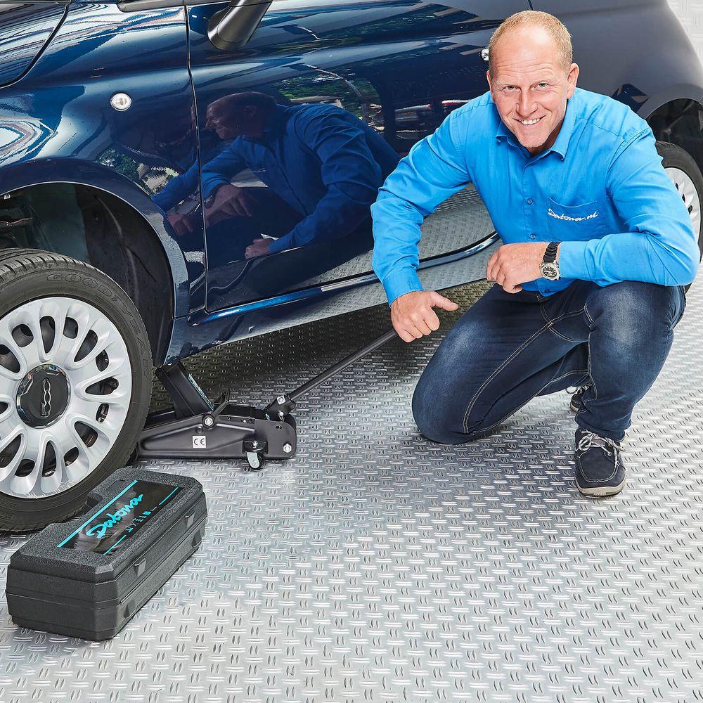 Krik 2 ton onder de auto met koffer