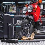 Werkplaats met rode brommer in de rijklem voor scooters