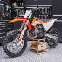 MX stand goud in werkplaats met KTM crosser
