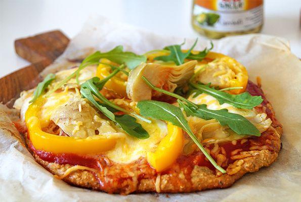Vegetarische pizza met artisjok, mozzarella, rucola en paprika